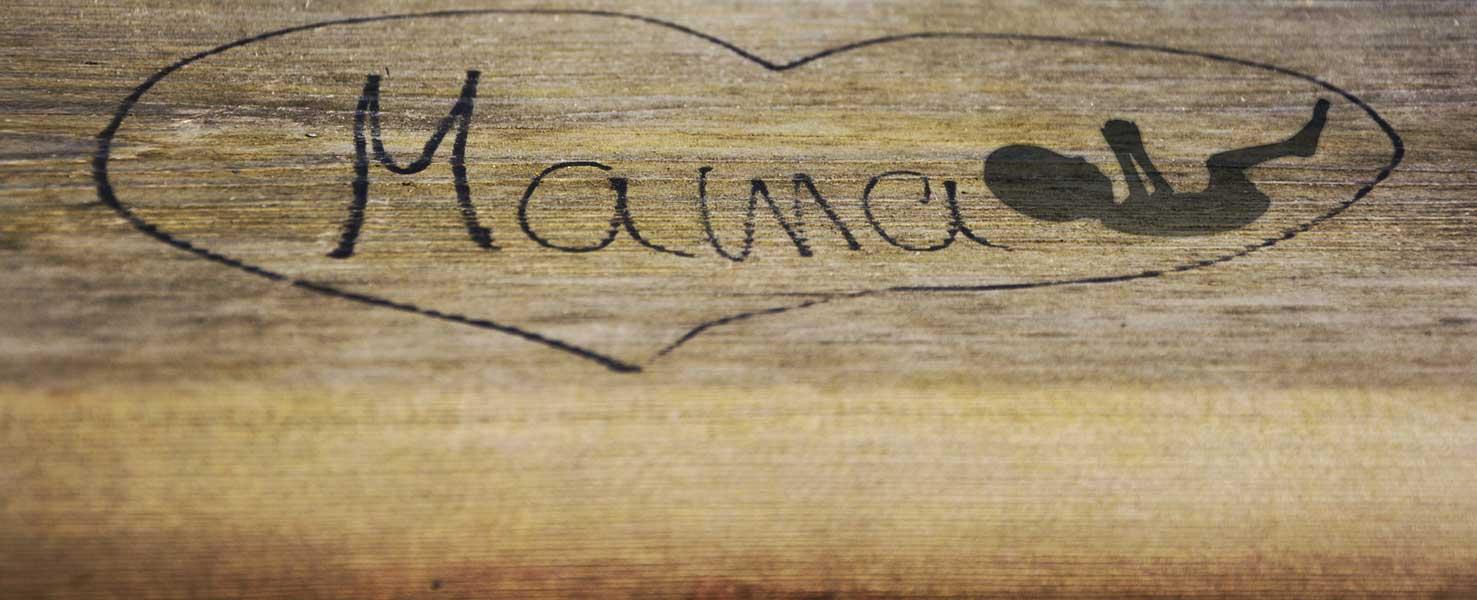 Mama-Schriftzug mit Fötus eingerahmt mit einem Herz auf Holz